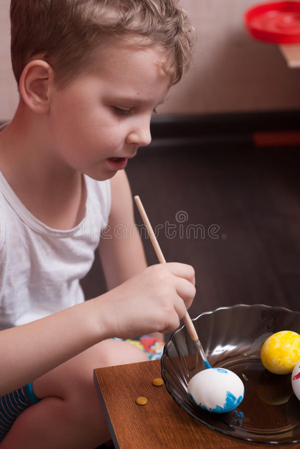 A little boy paints the eggs on the eve of Easter, colorful paints and brush, stock photography