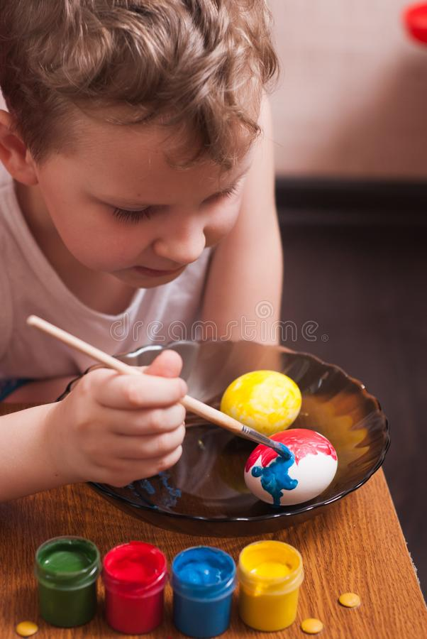 A little boy paints the eggs on the eve of Easter, colorful paints and brush, royalty free stock photo
