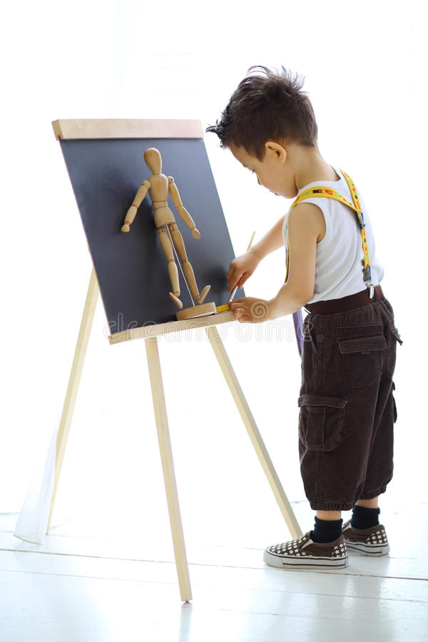 A little boy paints the wooden man royalty free stock photography