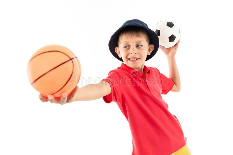 A little boy in panama, yellow jersey, red shorts and white sneakers stands with basketball and soccer balls stock images
