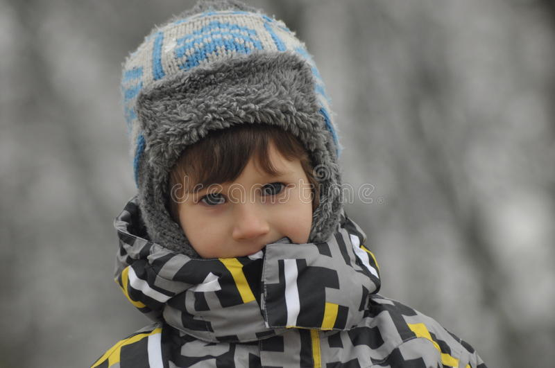 The little boy in the park in winter. Child in a cap and gloves royalty free stock image
