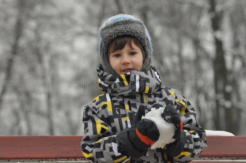 The little boy in the park in winter. Child in a cap and gloves. stock photography