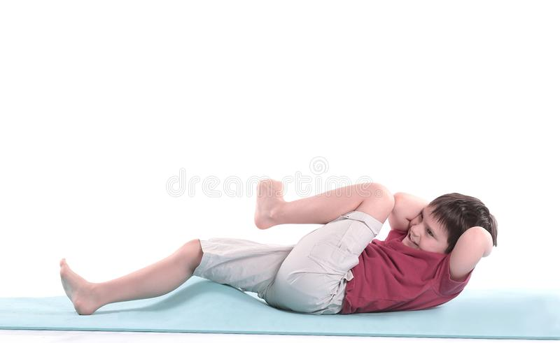 Little boy performs an exercise for the press.isolated on white stock photos