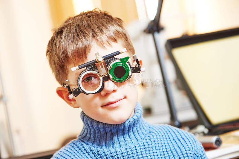 Little boy with phoropter at ophthalmology clinic. Ophthalmology concept. young boy with phoropter during sight testing or eye examinations in clinic royalty free stock photography