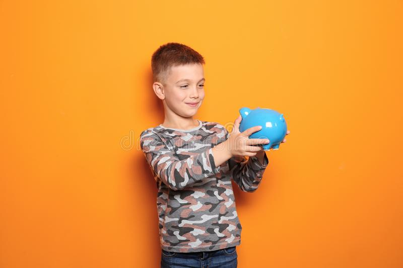 Little boy with piggy bank. On color background royalty free stock photo