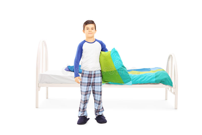 Little boy with pillow standing in front of a bed. Full length portrait of a little boy with pillow standing in front of a bed isolated on white background royalty free stock photography