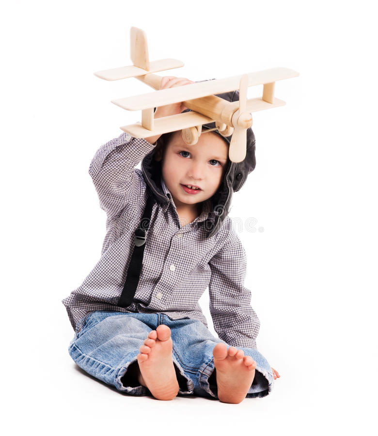 Little boy with pilot hat playing toy plane. Isolated on white background stock photo