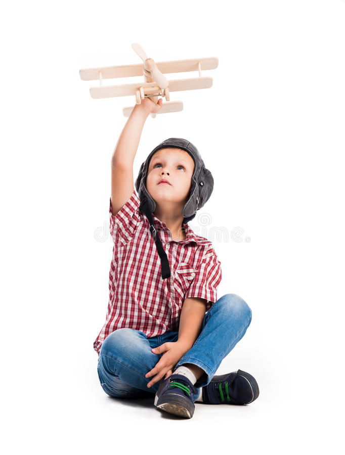 Little boy with pilot hat and toy airplane. Sitting isolated on white background royalty free stock images