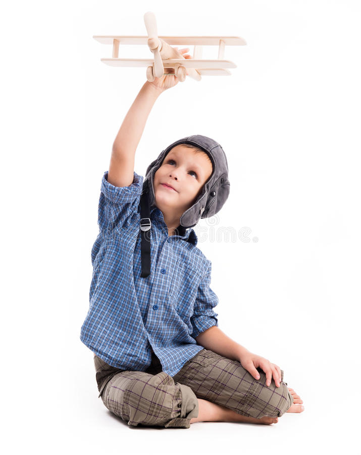 Little boy with pilot hat and toy airplane. Sitting isolated on white background stock photo