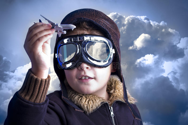 Little boy in the pilot`s hat. Boy as an old style pilot holding a toy airplane royalty free stock photo