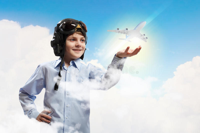 Little boy in pilot's hat. Image of little boy in pilots helmet with toy airplane in hand stock photo
