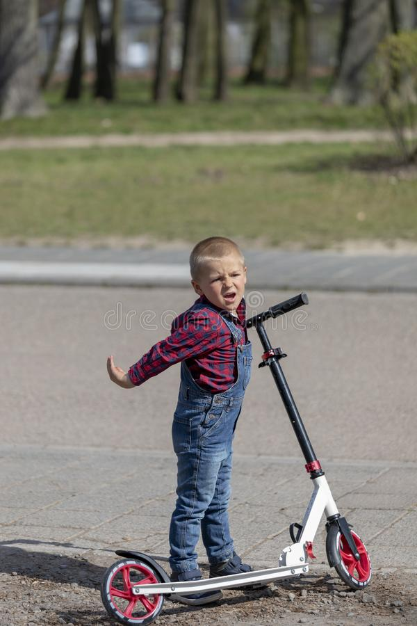 Little boy play balance scooter at spring in park.  royalty free stock images