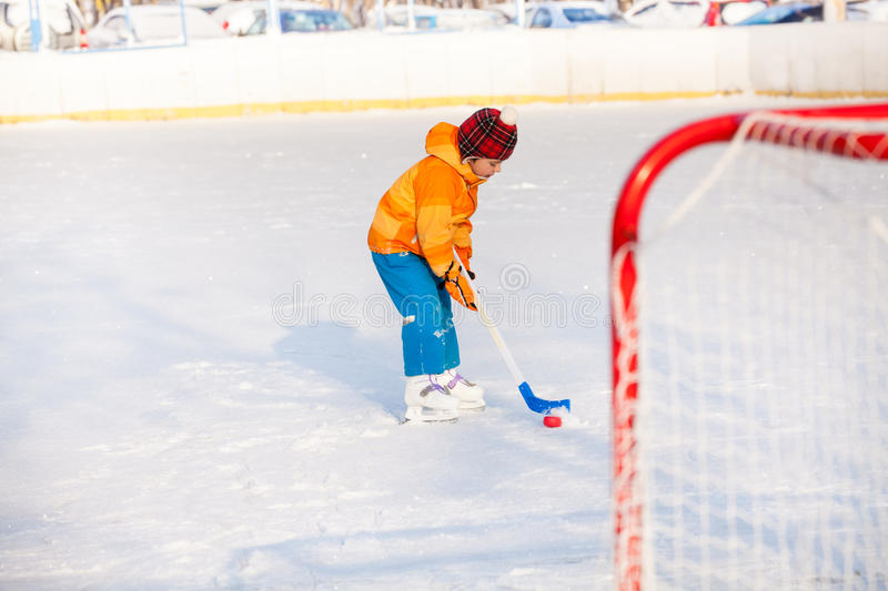 Little boy play ice hockey outside. Little boy play hockey punching with stick puck to the gates stock photography