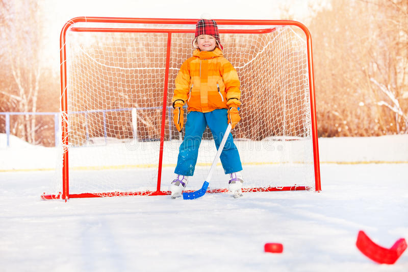 Little boy play ice hockey outside on winter day. Little boy with hockey stick stand in gates playing with friends royalty free stock photos