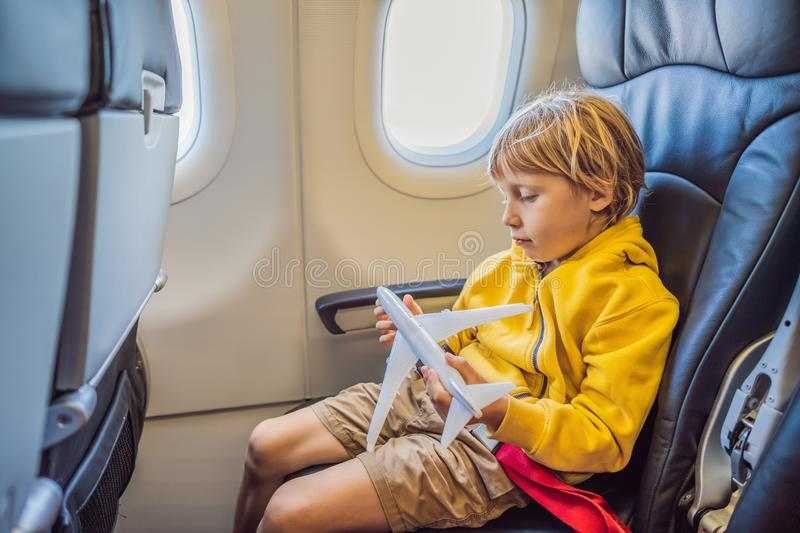 Little boy play with toy plane in the commercial jet airplane flying on vacation royalty free stock photos