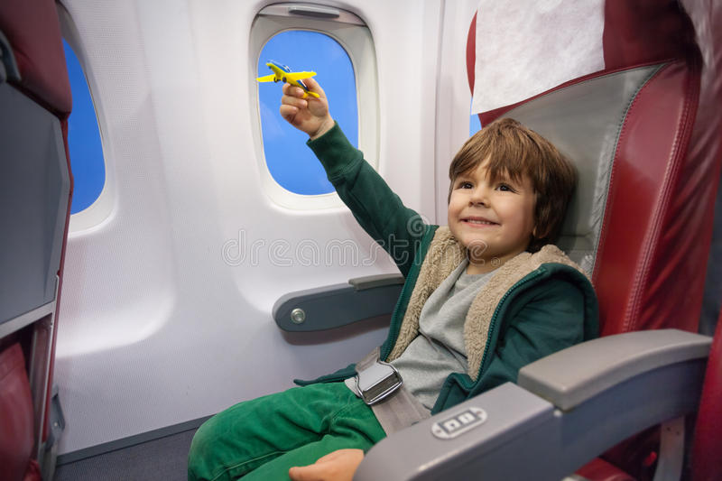 Little boy play with toy plane flying to vacation stock photo