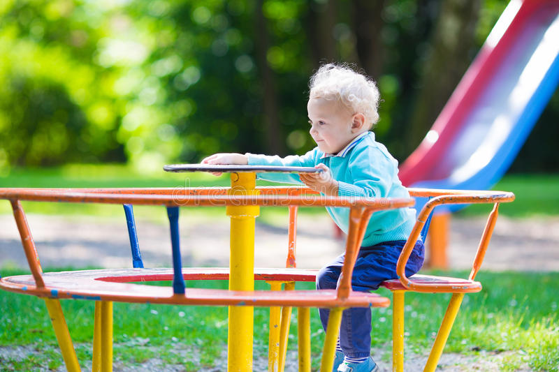 Little boy on a playground. Child playing outdoors in summer. Kids play on school yard. Happy kid in kindergarten or preschool. Children having fun at daycare royalty free stock photography
