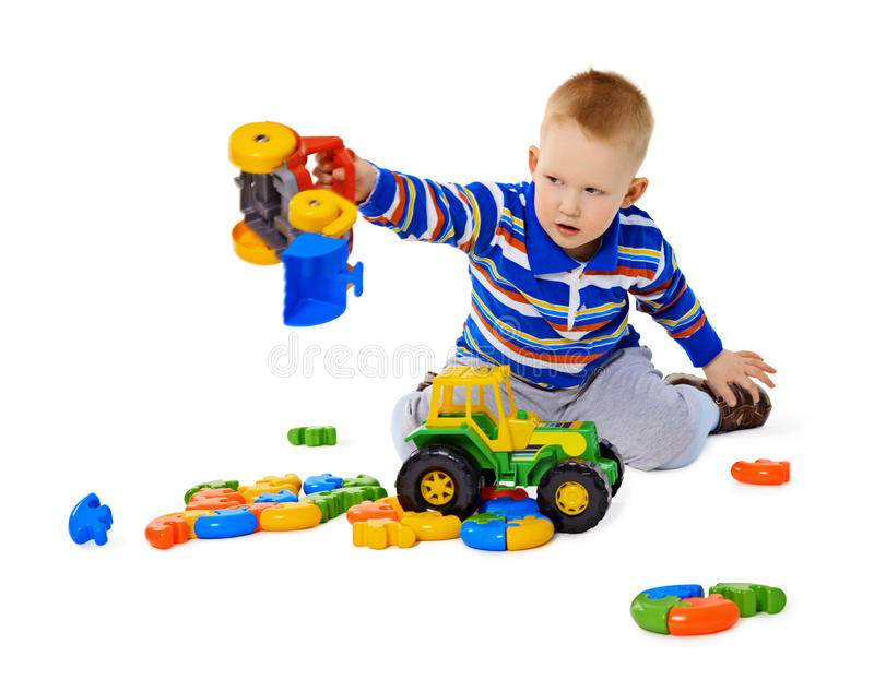 Little boy playing actively with plastic toys. Sitting on the floor stock image