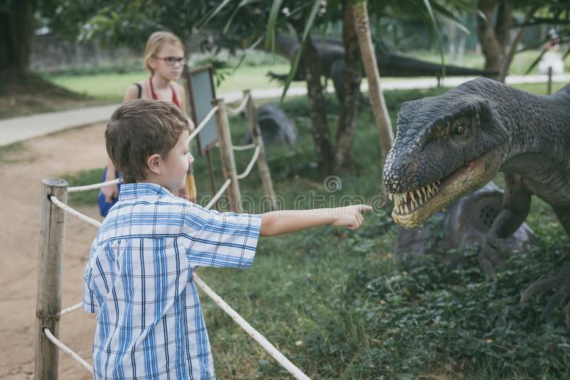 Little boy playing in the adventure dino park stock image