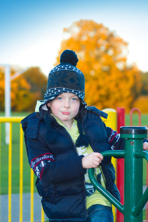 Little boy playing on appratus at the park stock photography
