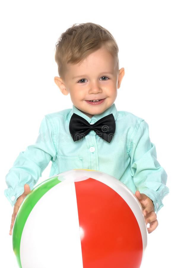 A little boy is playing with a ball. stock image