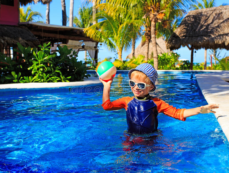 Little boy playing ball in swimming pool on beach. Little boy playing ball in swimming pool on tropical beach royalty free stock images