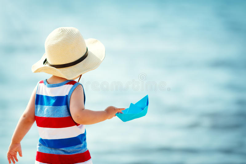 Little boy playing at the beach in straw hat. One year old boy playing at the beach in straw hat. Child with a paper ship at sea royalty free stock photos