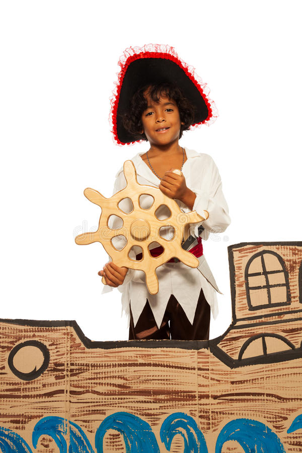 Little boy playing being pirate on cardboard ship. Boy playing to be a pirate standing and steering helm in the cardboard ship, isolated on white stock photos