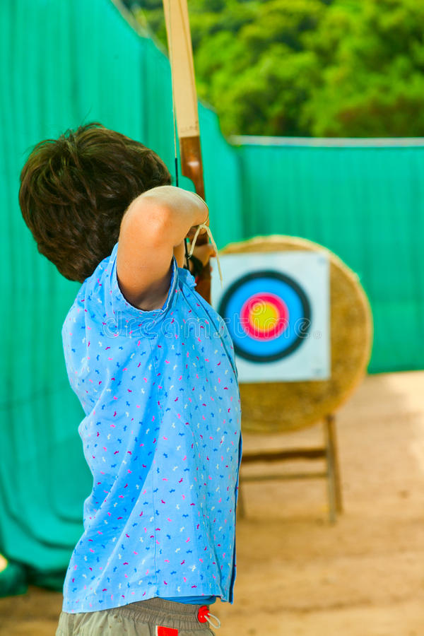 Little boy playing with bow and arrows. Child pulls with the arc stock photography