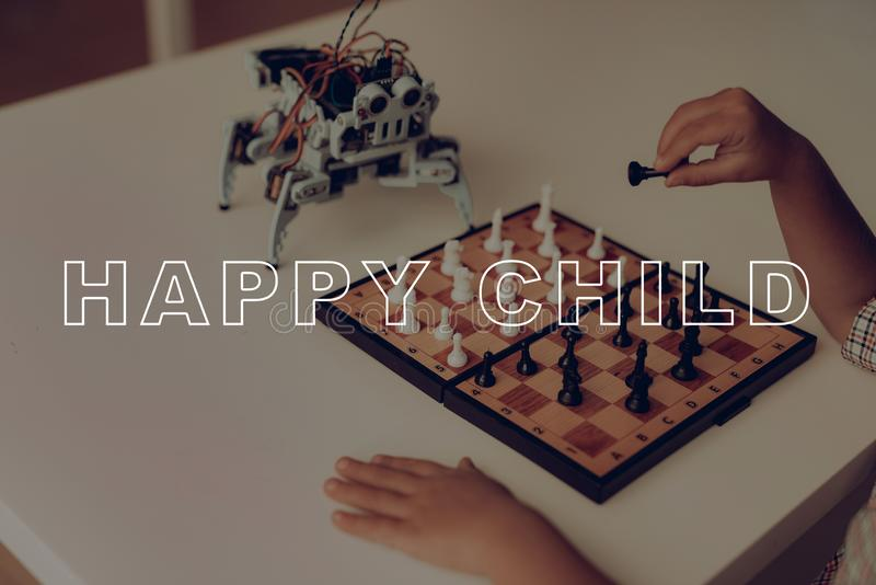 A Little Boy Is Playing Chess With A Gray Robot. stock photography