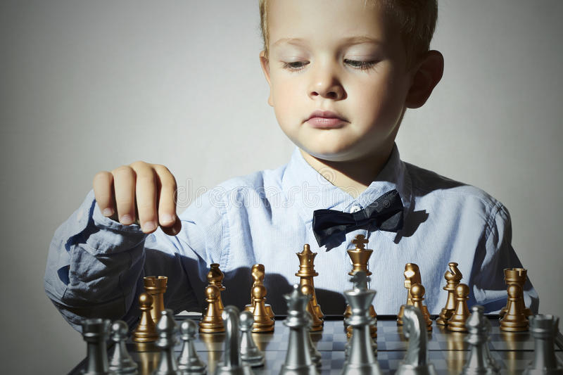 Little boy playing chess.Smart kid.genius Child. Intelligent game.Chessboard. Little boy playing chess.Smart kid.fashion children.5 Years Old Child in Bow-tie stock image