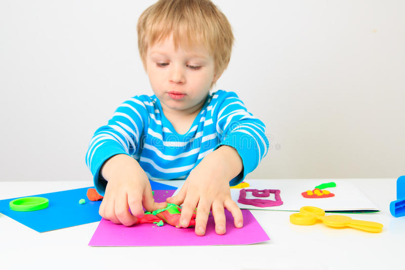 Little boy playing with clay dough, education and daycare. Concept royalty free stock photos