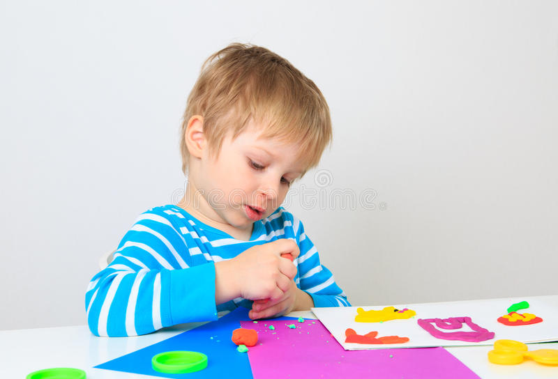 Little boy playing with clay dough, education and daycare. Concept stock images