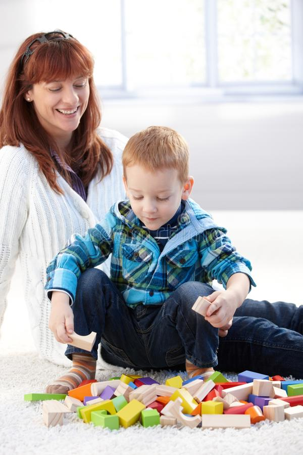 Little boy playing with cubes mother watching. Little boy playing at home with building cubes, mother watching, smiling happily royalty free stock image