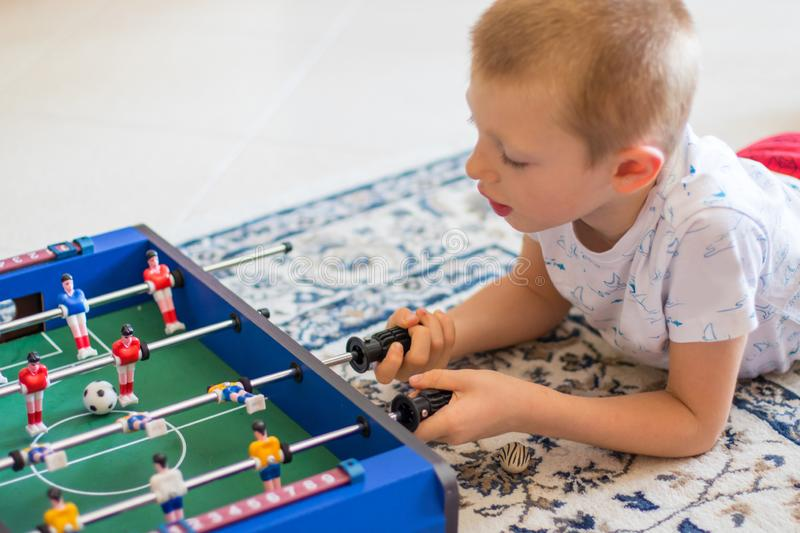 Little boy playing with foosball stock images