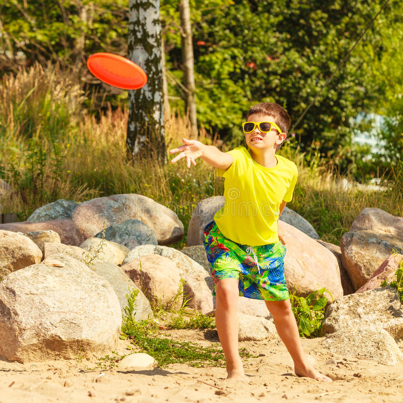 Little boy playing with frisbee disc. stock photos