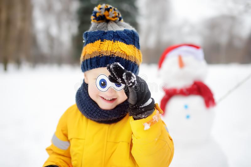 Little boy playing with funny snowman. Сhild tries on his eyes from snowman. Active outdoors leisure with children in winter stock photography