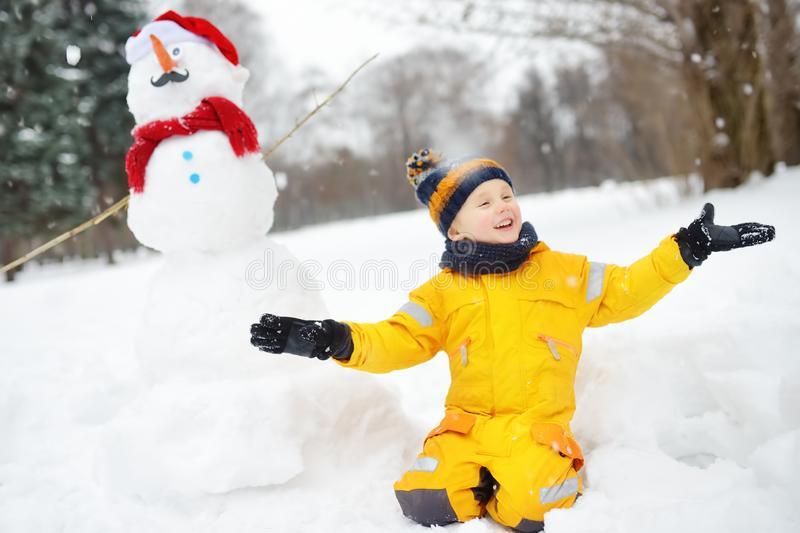 Little boy playing with funny snowman. Active outdoors leisure with children in winter stock photos