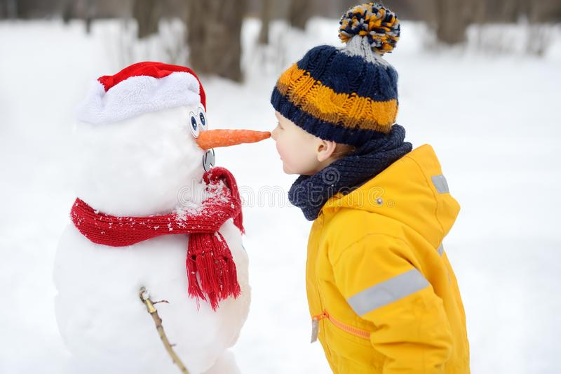 Little boy playing with funny snowman. Child reaches for a snowman`s carrot nose and wants to bite. Active outdoors leisure with royalty free stock image