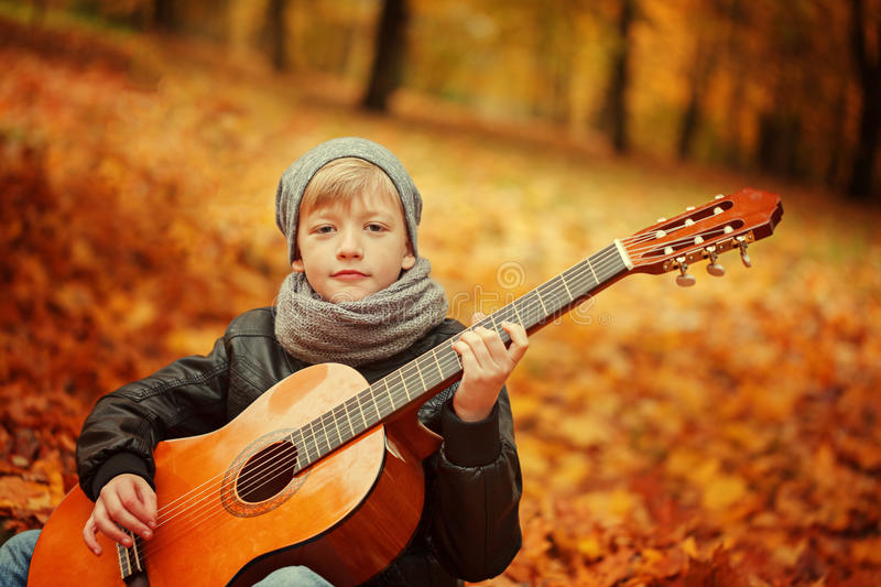 Little boy playing guitar on nature background, autumn day. Children's interest in music . stock image