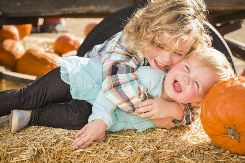 Little Boy Playing with His Baby Sister at Pumpkin Patch. Sweet Little Boy Plays with His Baby Sister in a Rustic Ranch Setting at the Pumpkin Patch stock photography