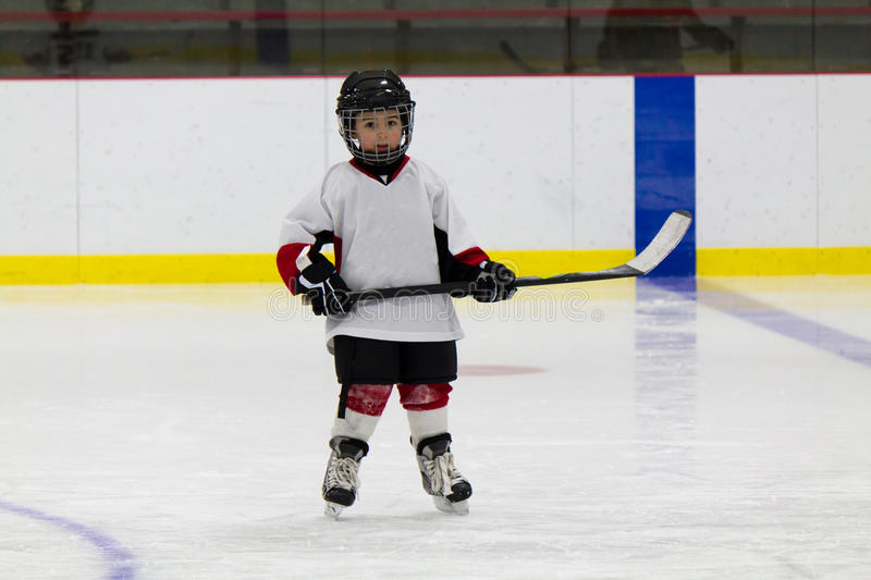 Little boy playing ice hockey stock photography