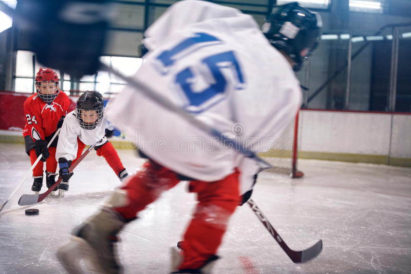 Little boy playing ice hockey. On the rink stock images