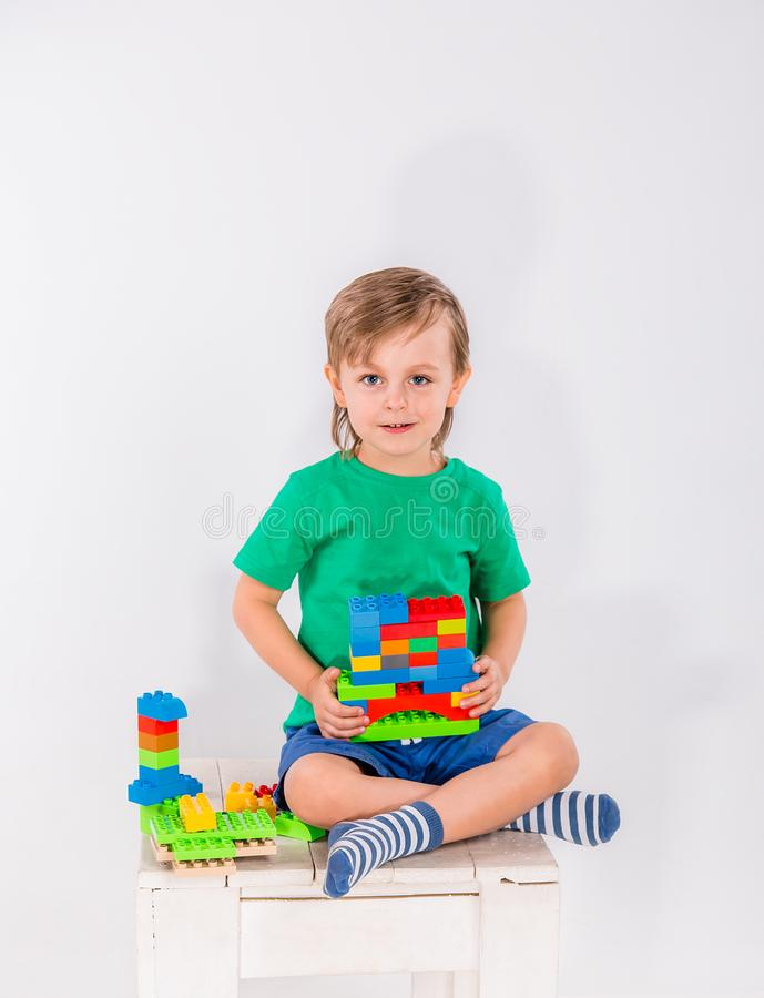 Little boy playing with lots of colorful plastic blocks constructor . royalty free stock photography