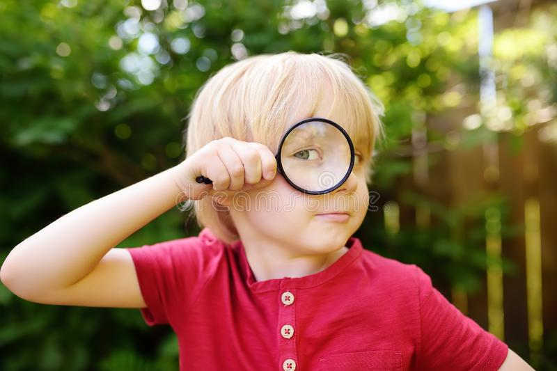 Little boy playing with magnifying glass. Little boy carefully looking at you with magnifier stock photos