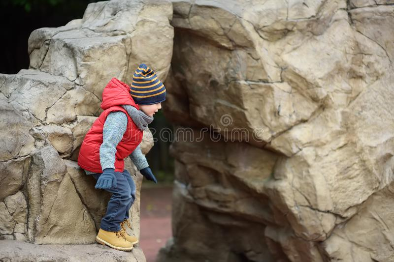 Little boy playing on natural kids play ground. Outdoors activities for family with kids in spring/autumn stock photo