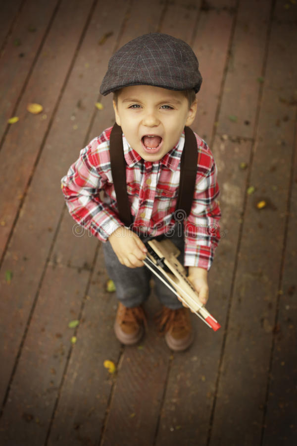 Little boy playing outdoor with a toy wooden gun stock images
