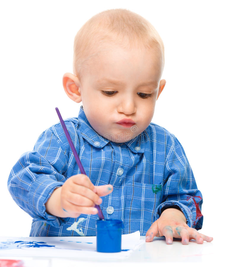 Little boy is playing with paints. Portrait of a cute little boy playing with paints, isolated over white royalty free stock image