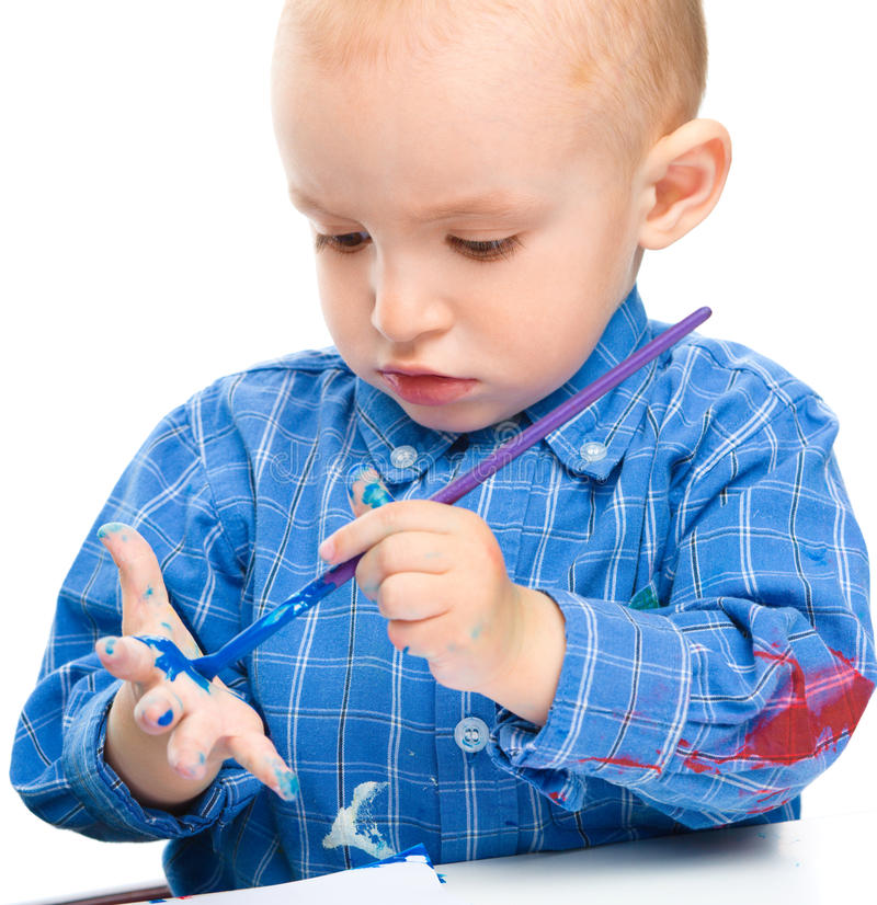 Little boy is playing with paints. Portrait of a cute little boy playing with paints, isolated over white stock photos