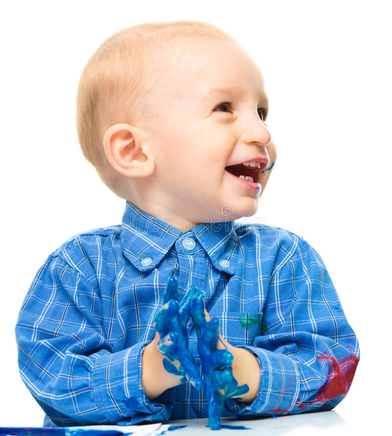 Little boy is playing with paints. Portrait of a cute little boy playing with paints, isolated over white stock photography
